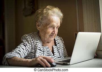 Old woman sitting with laptop at table in his house