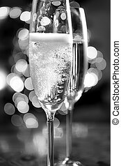 black and white photo of champagne poured into glasses -...