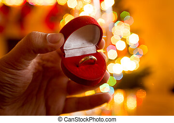 man presenting golden ring in box against decorated...