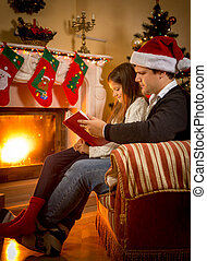 father sitting with daughter at fireplace and telling story...