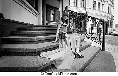 Black and white photo of elegant woman sitting on stone stairs