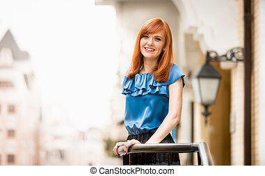 laughing redhead woman posing on street - Portrait of...