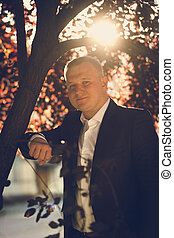 Toned portrait of man in suit posing under tree at sunny day...