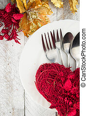 Valentine table setting in gold and red tone on wooden table