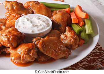 buffalo wings with cheese sauce and vegetables close-up....