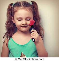 Fun beautiful small kid girl applying tonal cosmetic on the...