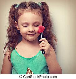 Fun beautiful small kid girl applying tonal cosmetic on the...