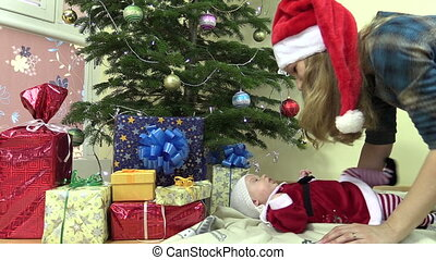 woman baby have fun - Playful mother with Santa hat play...