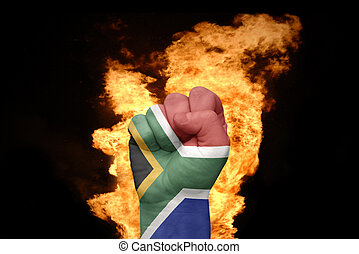 fire fist with the national flag of south africa - fist with...