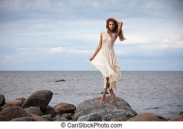 girl standing on stones against the sea - Beautiful girl in...