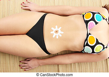 Young woman with sun-shaped sun cream isolated on white...