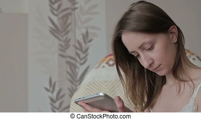 Woman at home relaxing in rocker, armchair and using tablet...