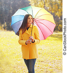 Beautiful young woman wearing a yellow coat with colorful...
