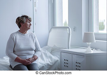 Ill lonely woman sitting on hospital bed