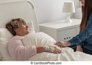 Girl caring about caring grandma staying in hospital