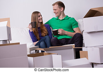 Packing up stuff - Young couple has a break during packing...