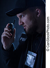 Policeman using walkie talkie - Portrait of angry policeman...
