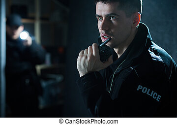 Talking on walkie talkie - Policeman at action talking on...