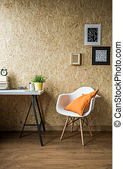 White chair with orange cushion in wooden interior