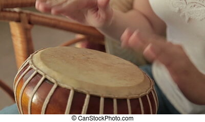 Woman banging a bongo, HD