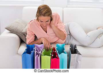 Woman On Sofa Looking At Shopping Bags