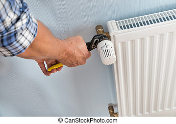 Plumber Fixing Radiator With Wrench