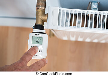 Person Hand Adjusting Temperature On Thermostat