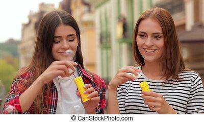 Beautiful young girls blowing bubble outdoor - Beautiful...