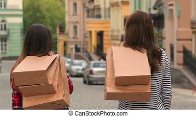Girls with shopping bags on city street