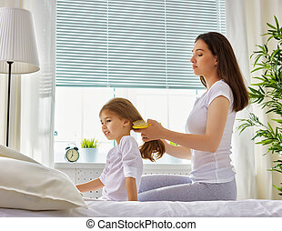 mother with her child - mother combing her daughter's hair