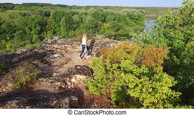 Aerial: woman climbs on top of rock