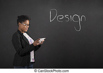 African woman with tablet designing something on blackboard...