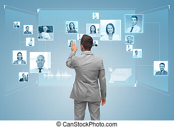 businessman with contacts icons on virtual screen