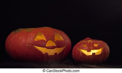 Two halloween pumpkins spew smoke - Black background with...