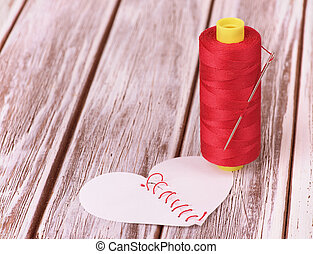 needle and thread on wooden background