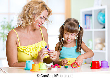 mother teaches child to work with colorful play clay toys