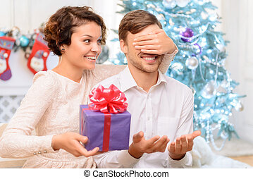 Loving couple holding present - Present for you. Positive...