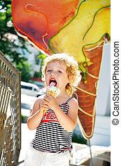 girl love ice cream - lovely little girl outdoors eating...