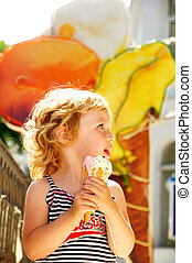 girl eating ice cream cone - little girl outdoors eating...