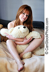 pretty redheaded girl sitting on the bed