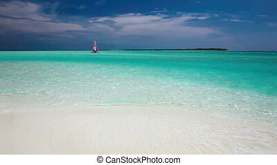 Sailing boat seen from beach - Sailing boat with red sail on...