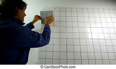 tiler - Worker distributes the mass of the tile glue cement...