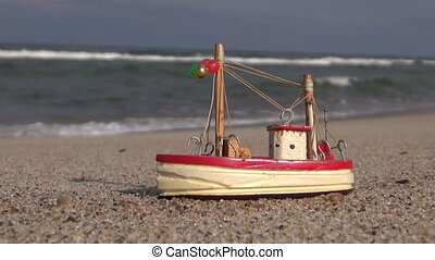 Wooden ship model toy by the sea on beach sand