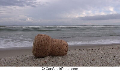 Champagne cork lying on beach sand - Champagne cork lying on...