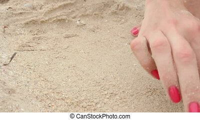 Female hand draw on the sand sea
