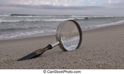 Magnifying glass on the beach - Old magnifying glass with...