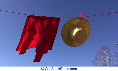 wicker hat and a red shirt on rope - A wicker hat and a red...