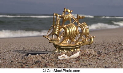 decorative toy brass ship in sand - Seascape with decorative...