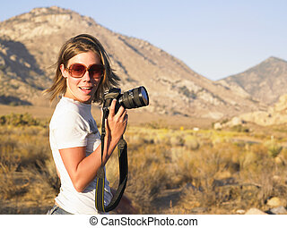 Young Woman Wearing Sunglasses Holding Camera - Young woman...
