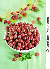 Red gooseberries in white bowl on green wooden table